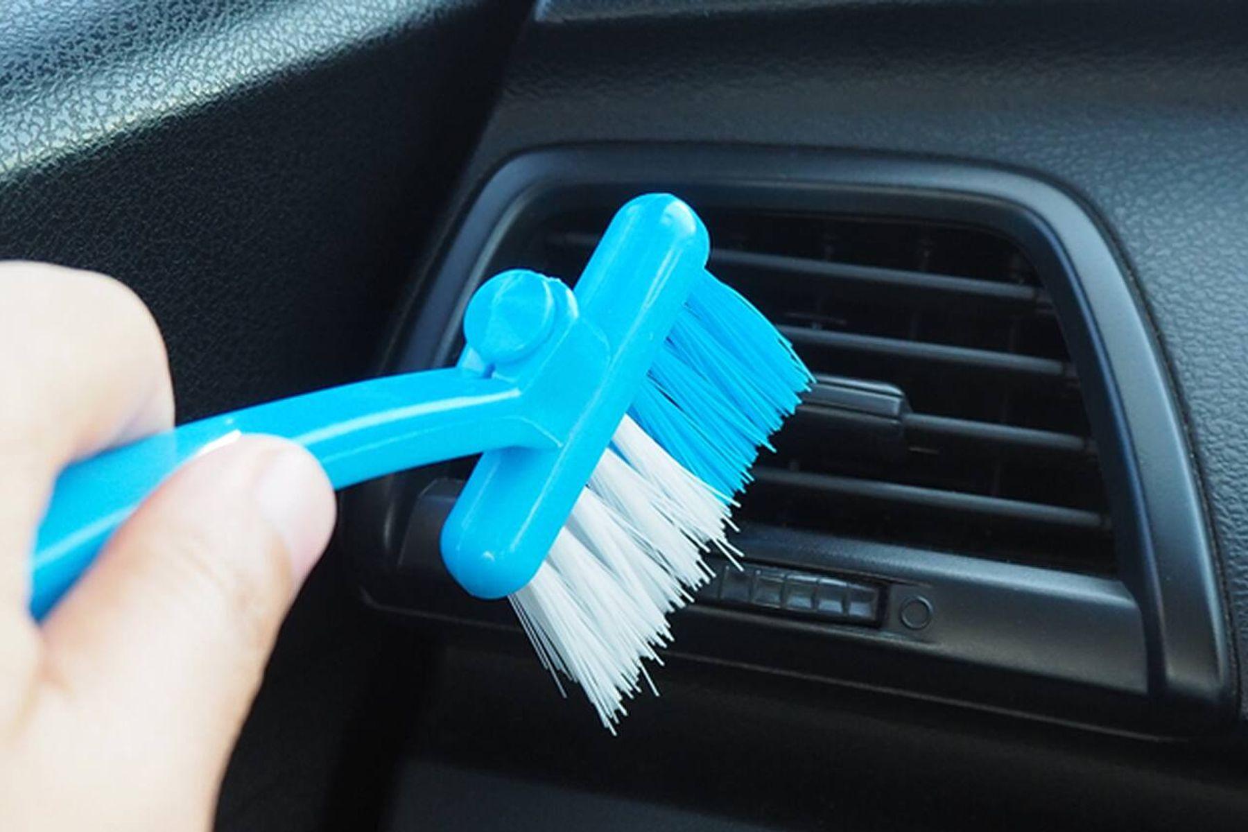 Pessoa limpando a saída de ar do carro para eliminar odores e tirar cheiro do carro