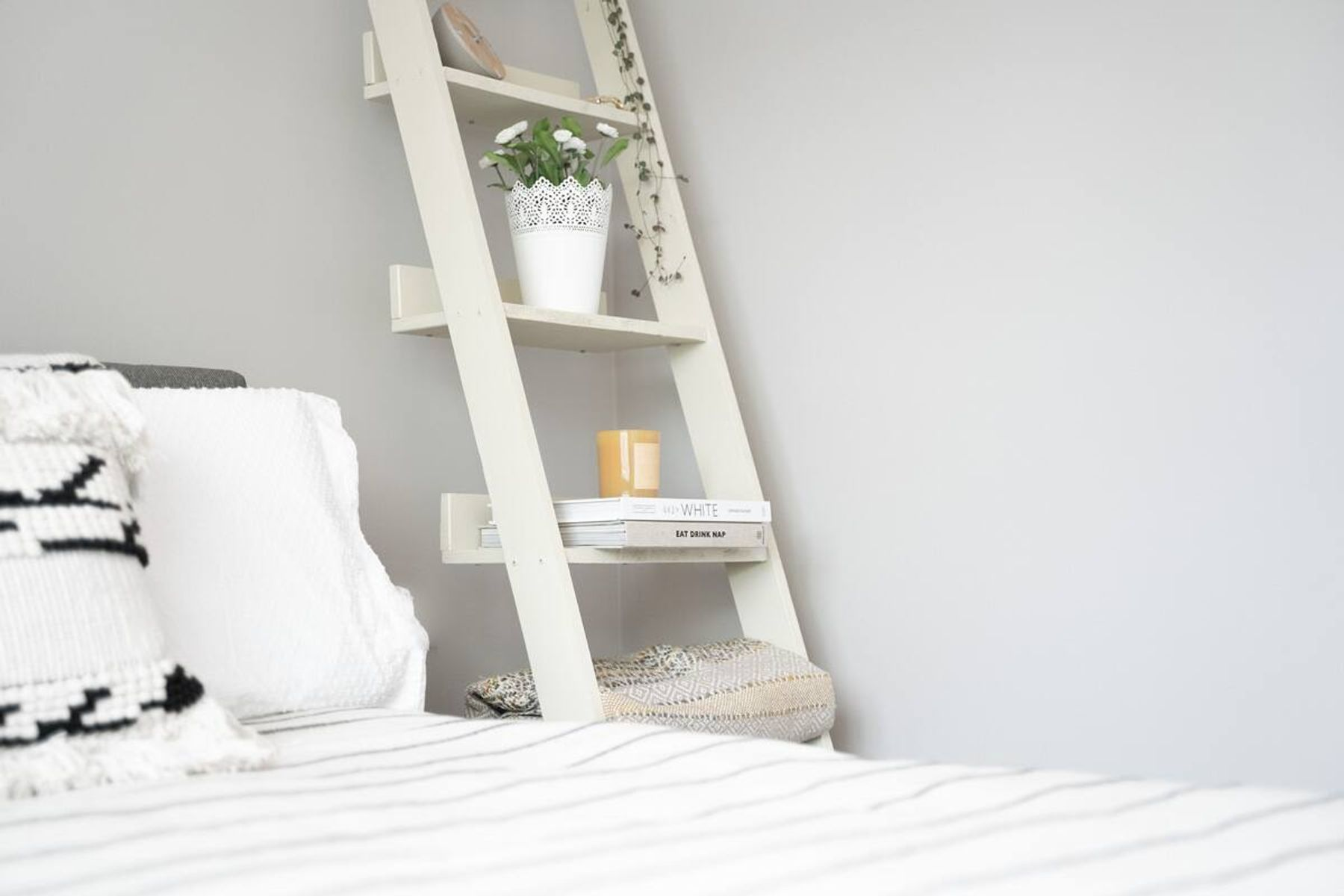 A wooden ladder shelf beside a bed