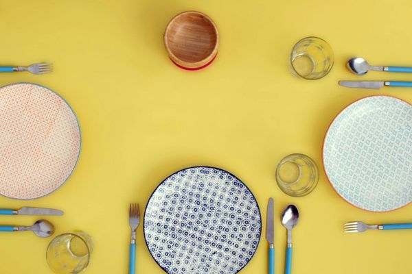 pratos, copos e talheres organizados sobre uma mesa amarela