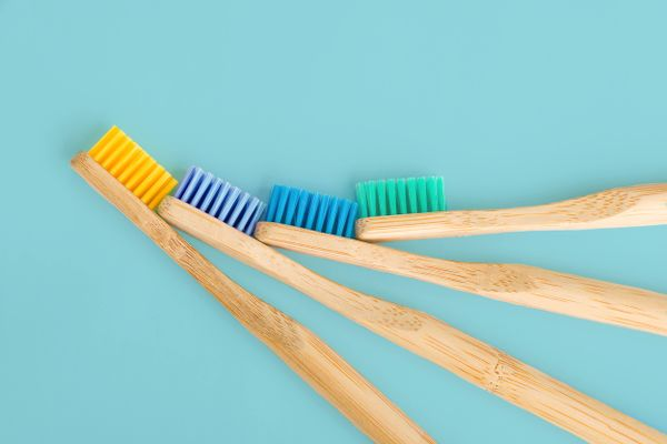 four wooden toothbrushes in different colours