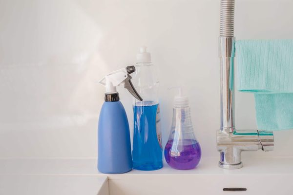 Waschmittel, Sprays, Reinigungsmittel und Lappen auf der Waschtischplatte