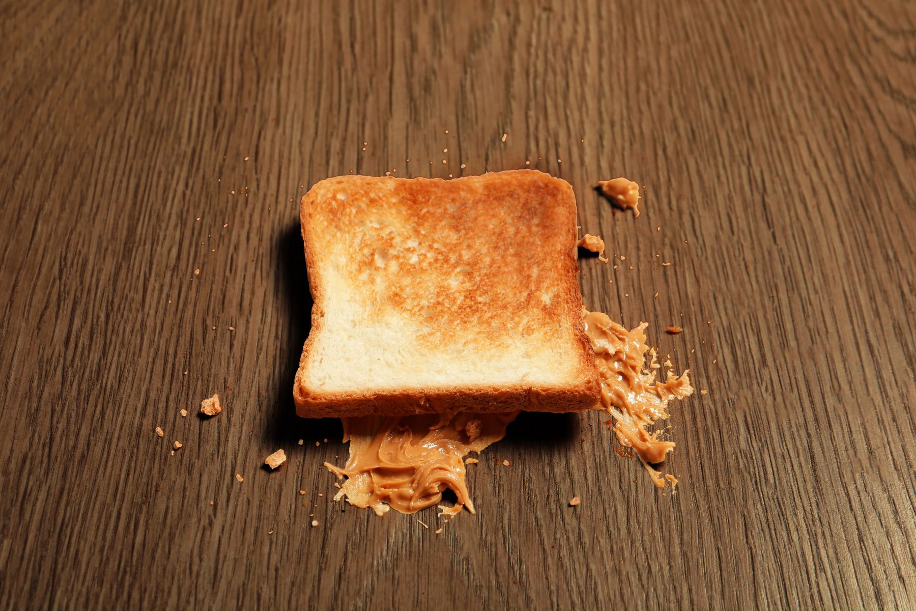 A slice of peanut butter toast on wooden floor