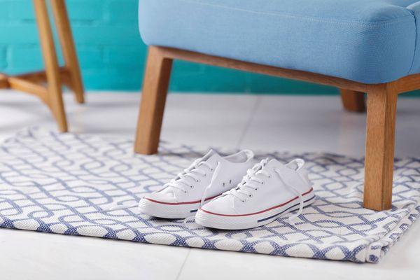 Par de tênis branco em frente a uma poltrona azul com pés de madeira