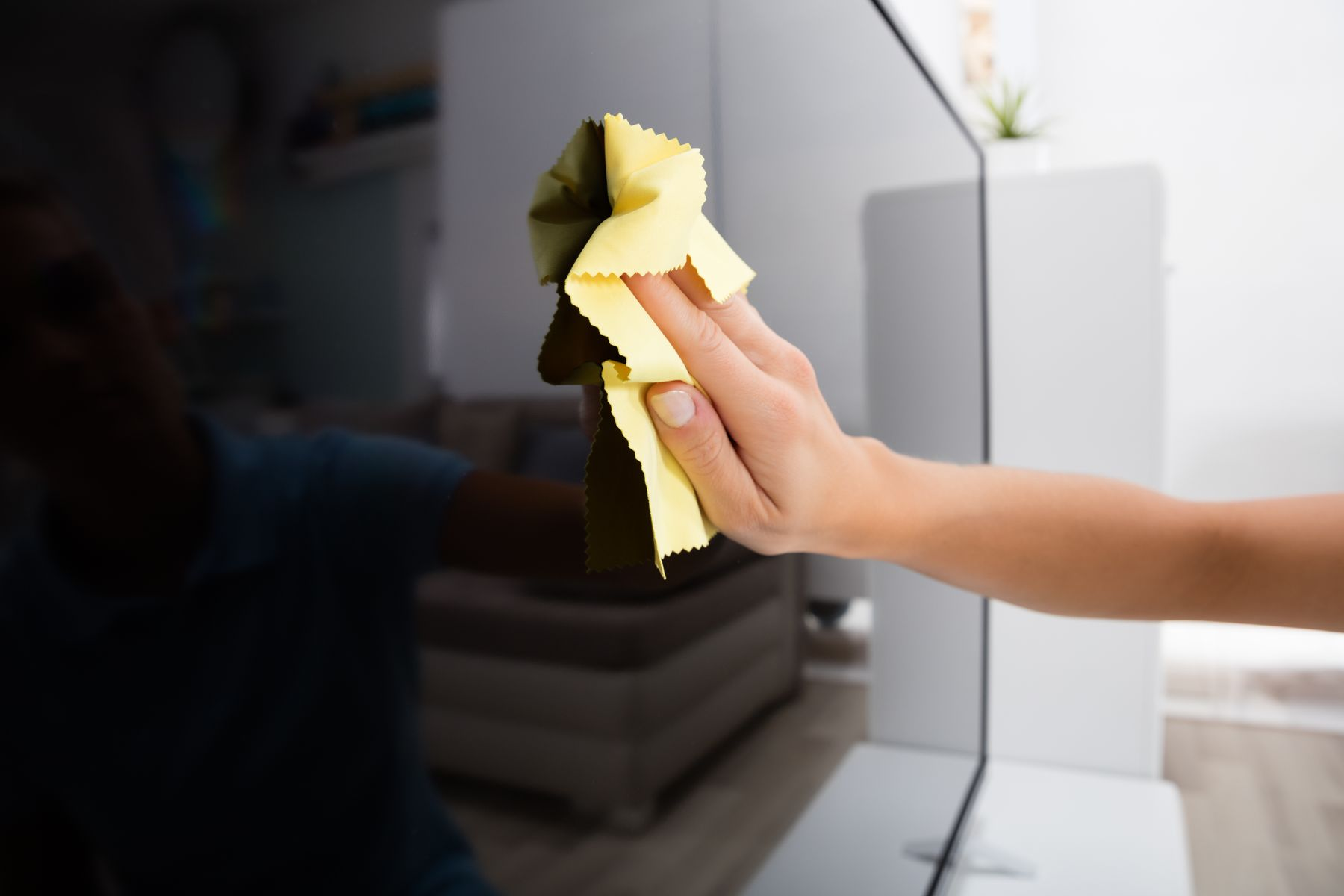 hand using yellow cloth to clean tv screen
