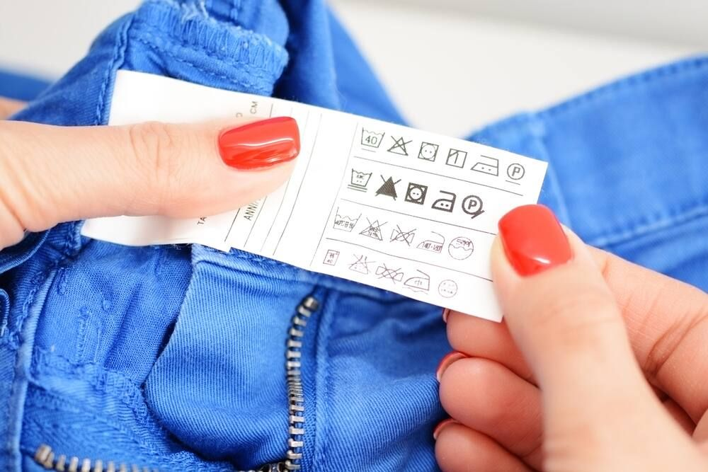 A care label is being checked on a bright blue pair of jeans