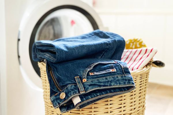 A pair of jeans on top of a laundry basket in front of a washing machine