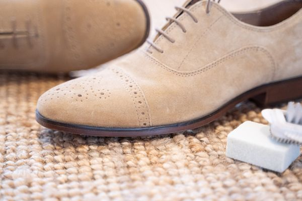 A pair of nubuck leather shoes with some cleaning equipment