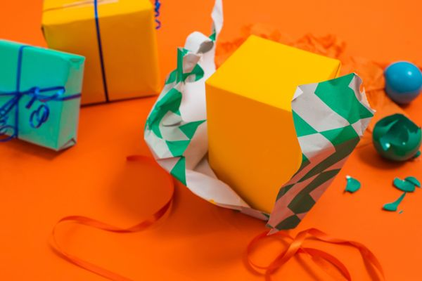 Unwrapped presents against orange backdrop