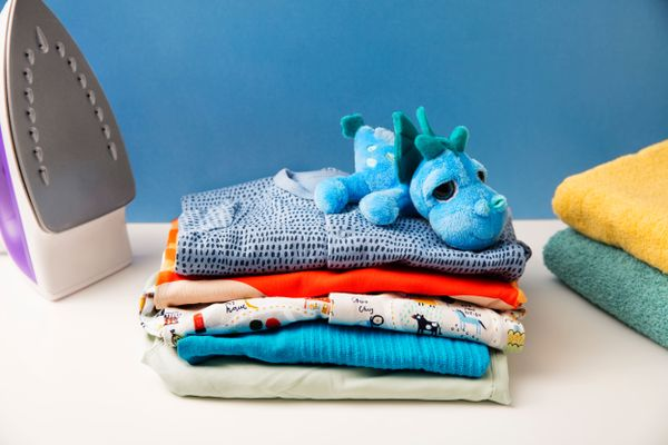 baby essentials and clothes on the table against blue wall