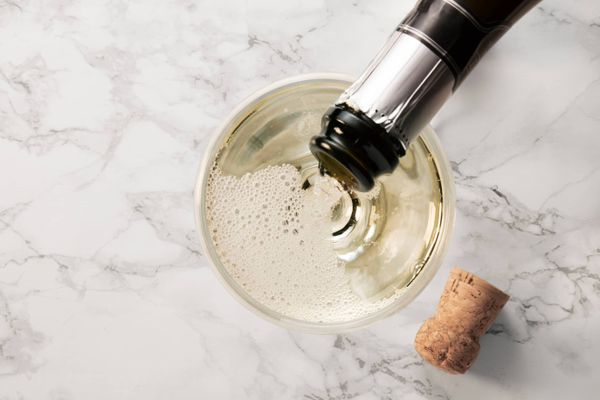 bachelorette party ideas: champagne being poured into glass on marble worktop