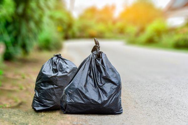czarne worki na śmieci zamknięte i umieszczone na krawędzi asfaltu