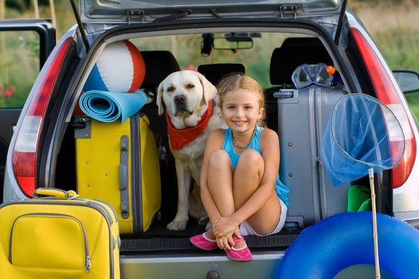 Mädchen mit Hund und Reisetaschen im Kofferraum