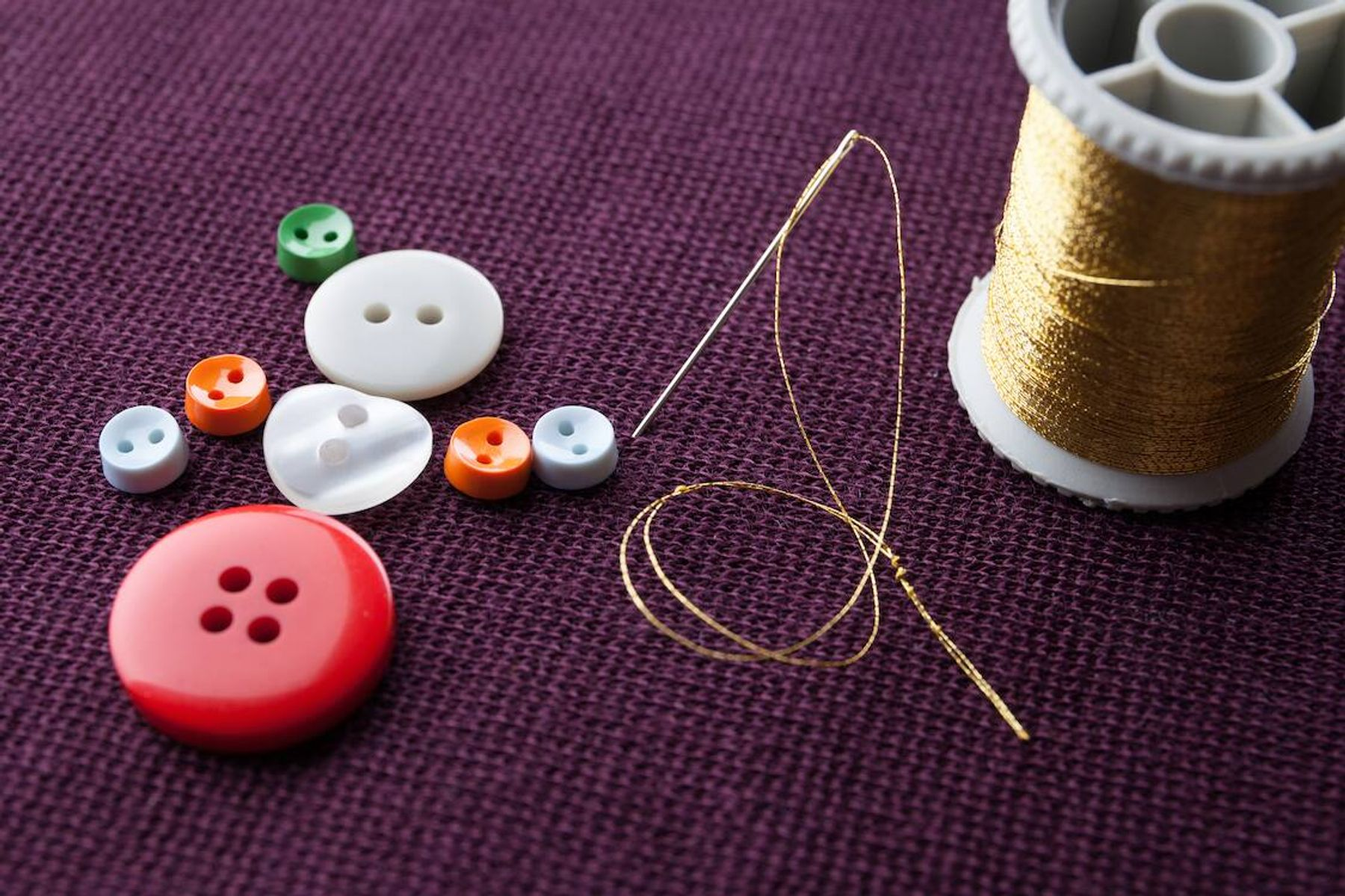 Buttons and thread on a purple background