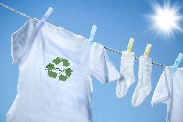 Remera blanca con símbolo de reciclaje colgada en tendedero