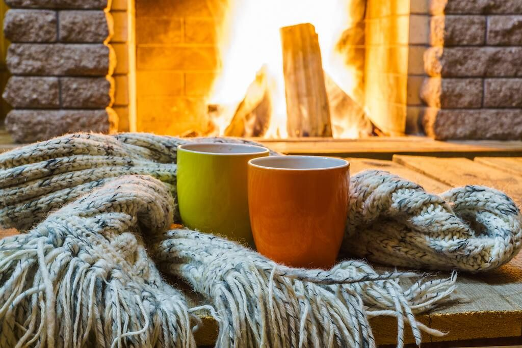 How to clean soot from brick : fireplace with a blanket and mugs