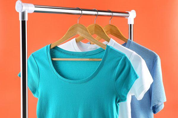 Varal de ferro com três camisetas penduradas