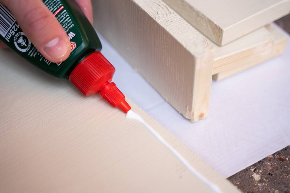 A line of wood glue being applied to the back of a wood panel