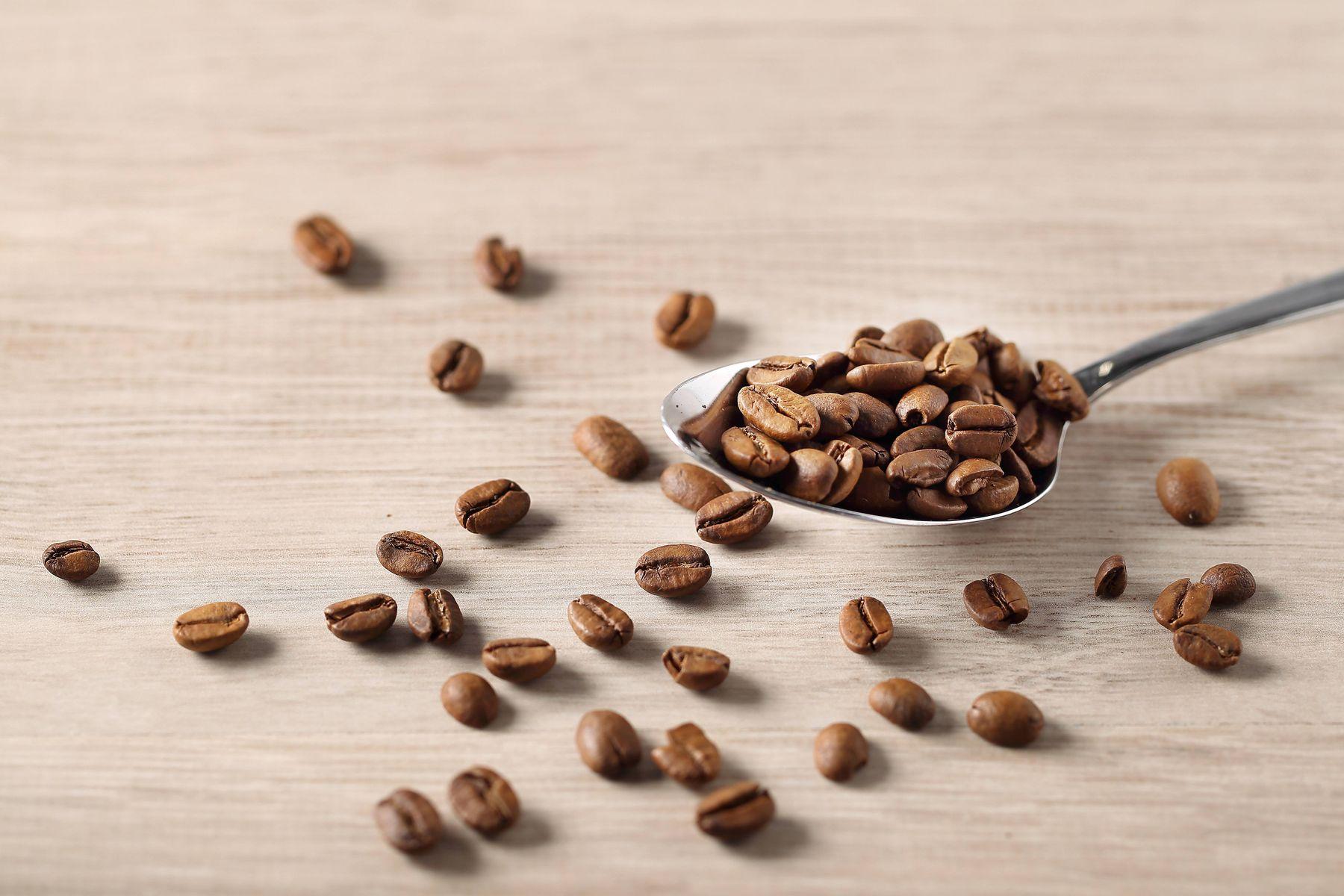 kávová zrna na lžíci a na stole