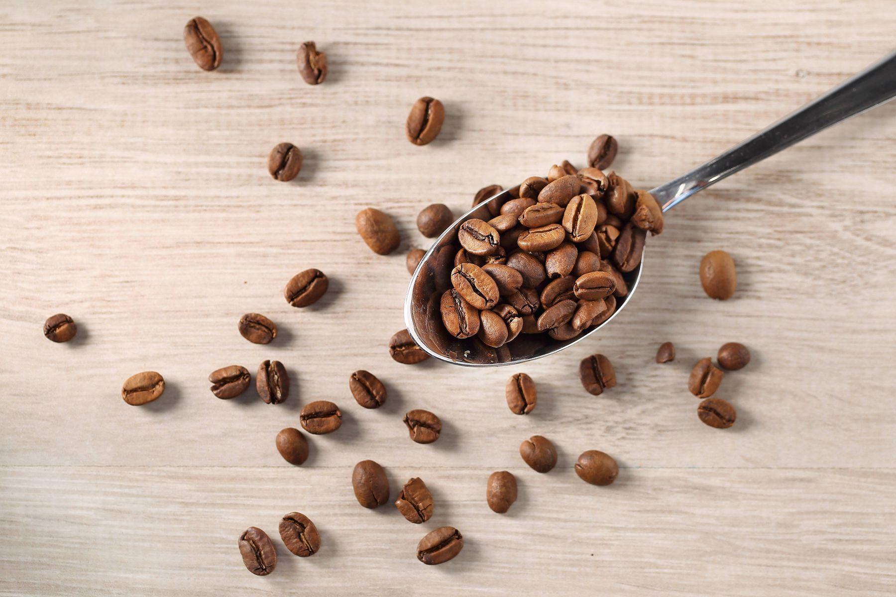 Grãos de café em cima de mesa de madeira