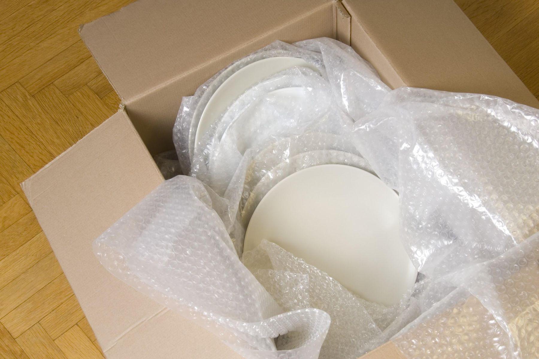 Pratos de louça e plástico bolha em caixa de papelão