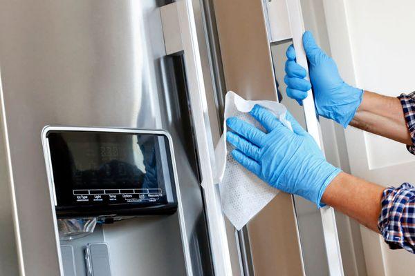 Beyaz bir bezle buzdolabını temizleyen mavi eldivenli bir kişi