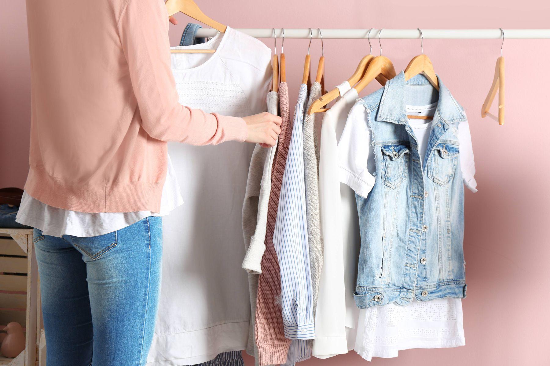 mulher segura cabide com camiseta branca perto de arara de roupas com blusas, camisetas e colete jeans, em fundo rosa