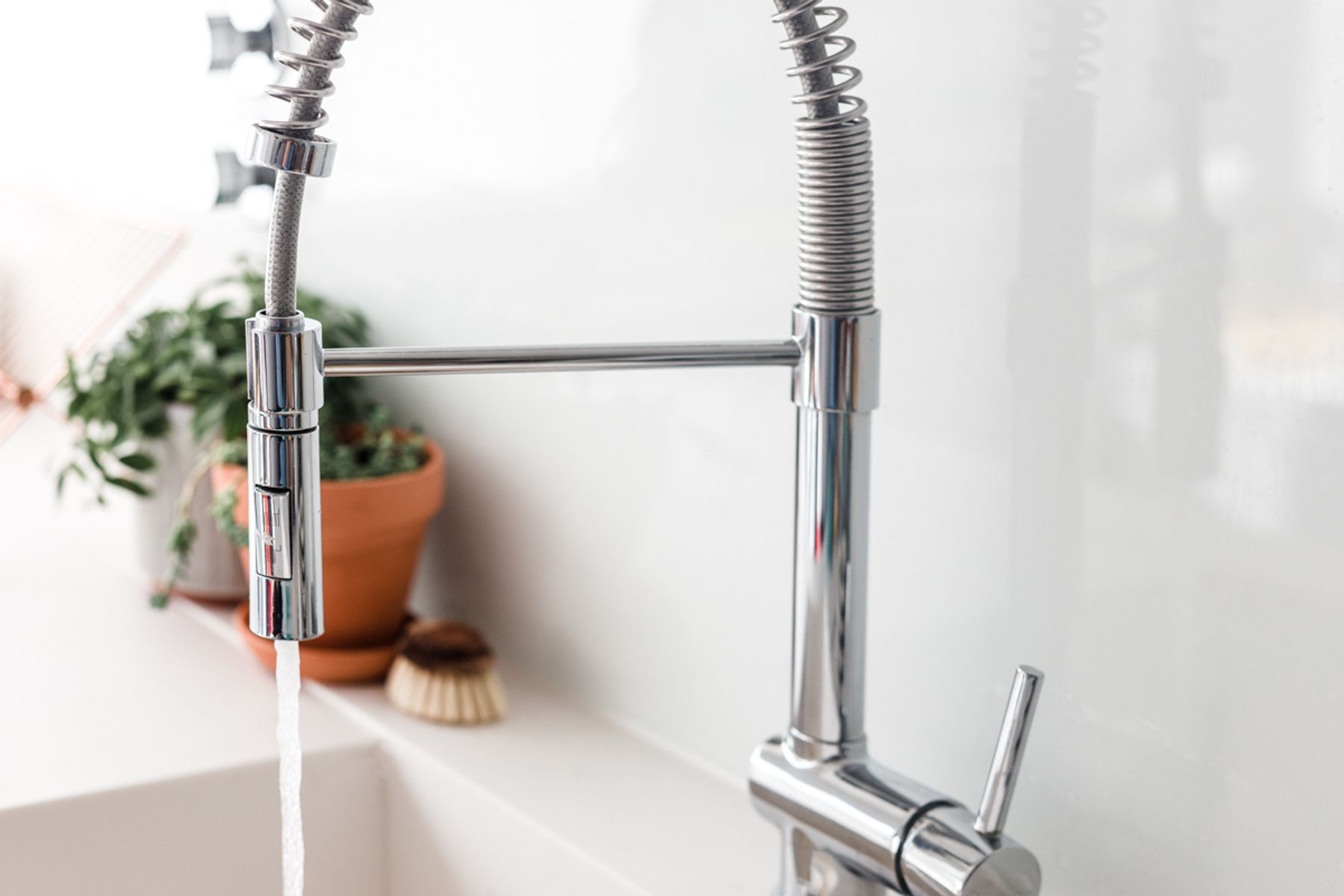 Water flowing out of a chrome kitchen tap.