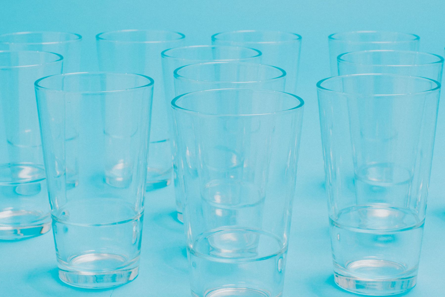 Several clean tumblers on blue background after removing stains and labels from the glass