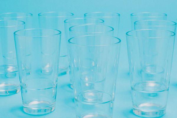 Vários copos de vidro transparentes em fundo azul