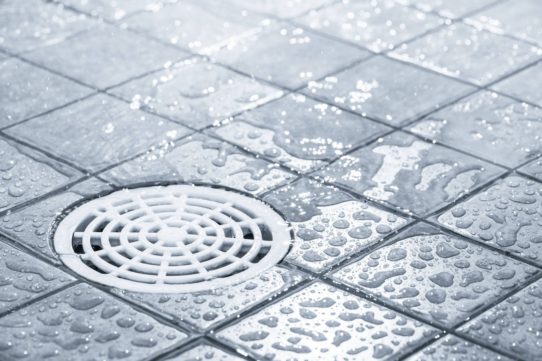 a white drain in a tiled silver floor