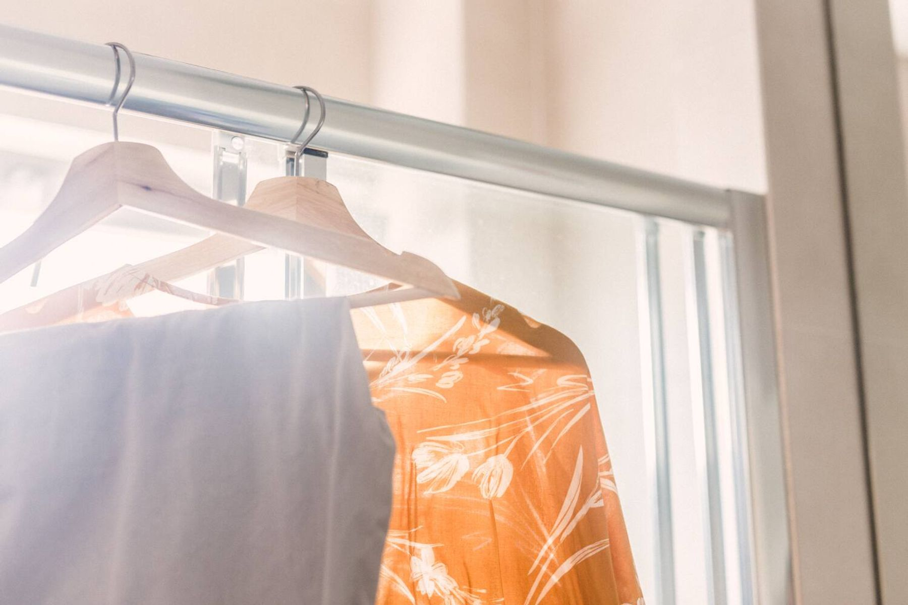 orange shirt with flower details and white pants on hangers in the bathroom stall