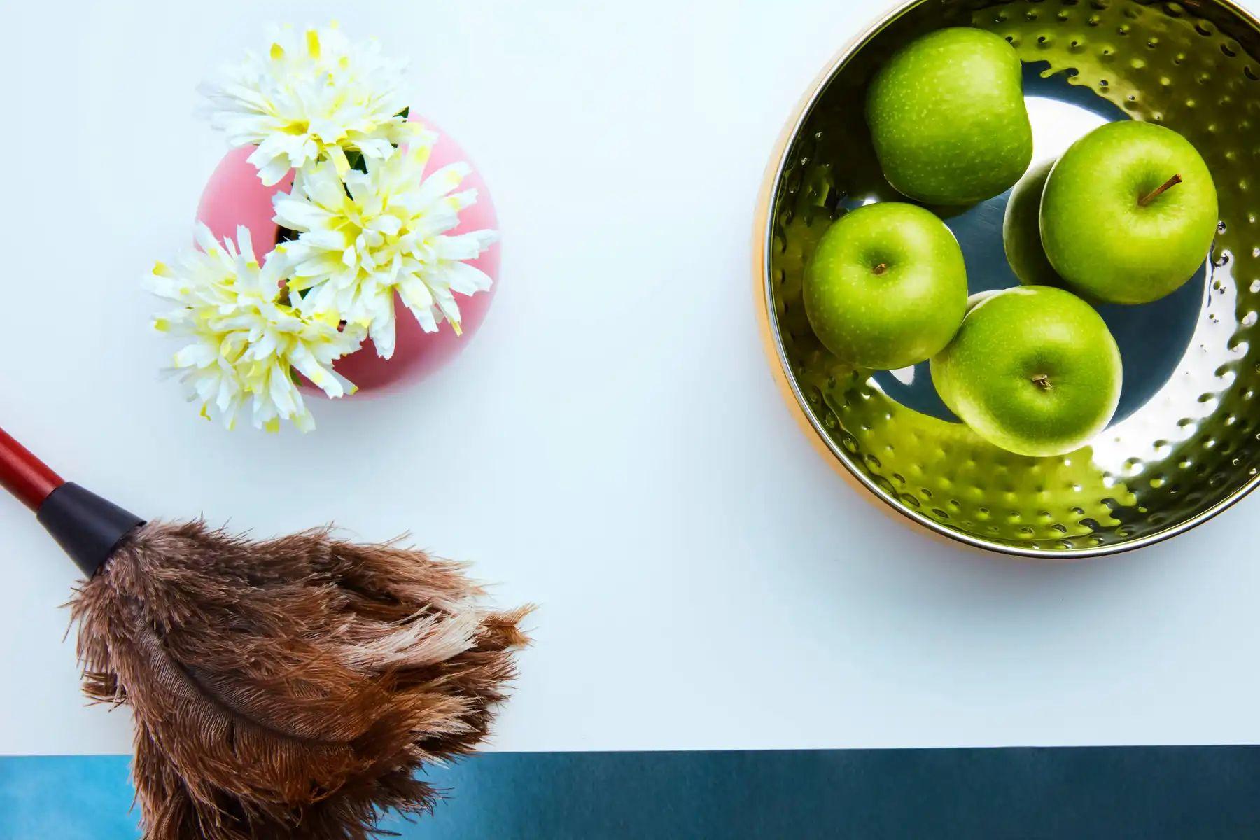 Manzanas verdes, flores blancas y plumero