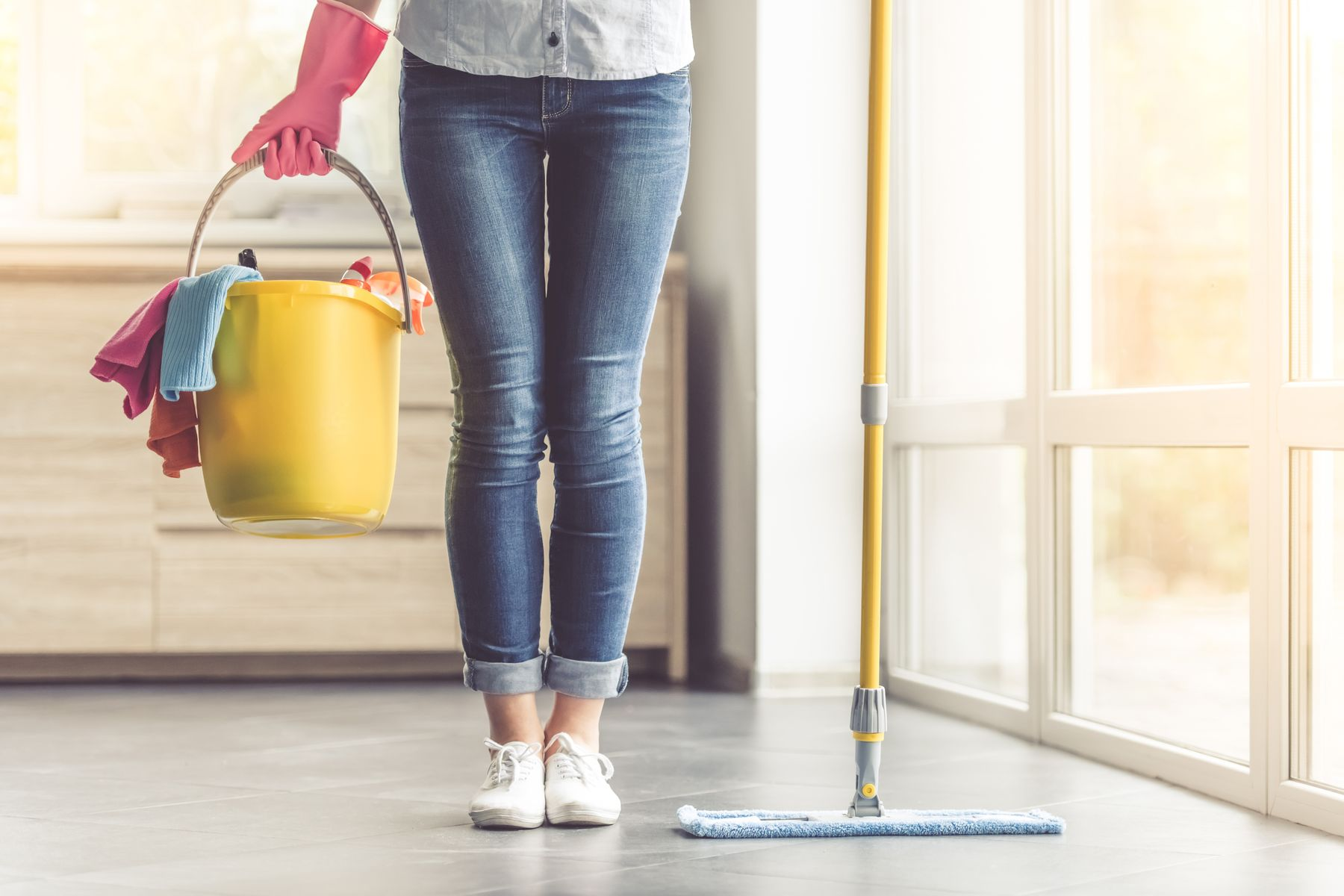 woman in jeans holding bucket of cleaning supplies and mop