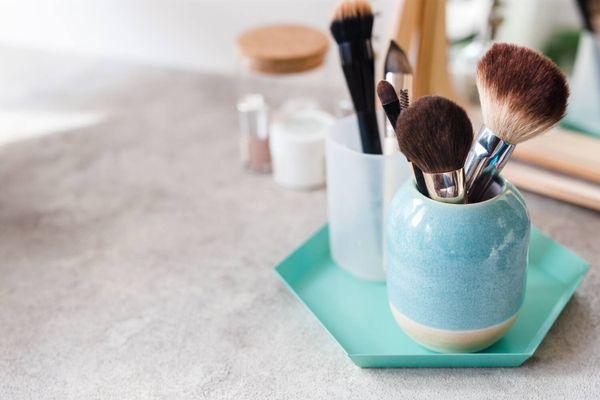 Pincéis de maquiagem organizados em vidros e potes cerâmicos sobre uma bandeja