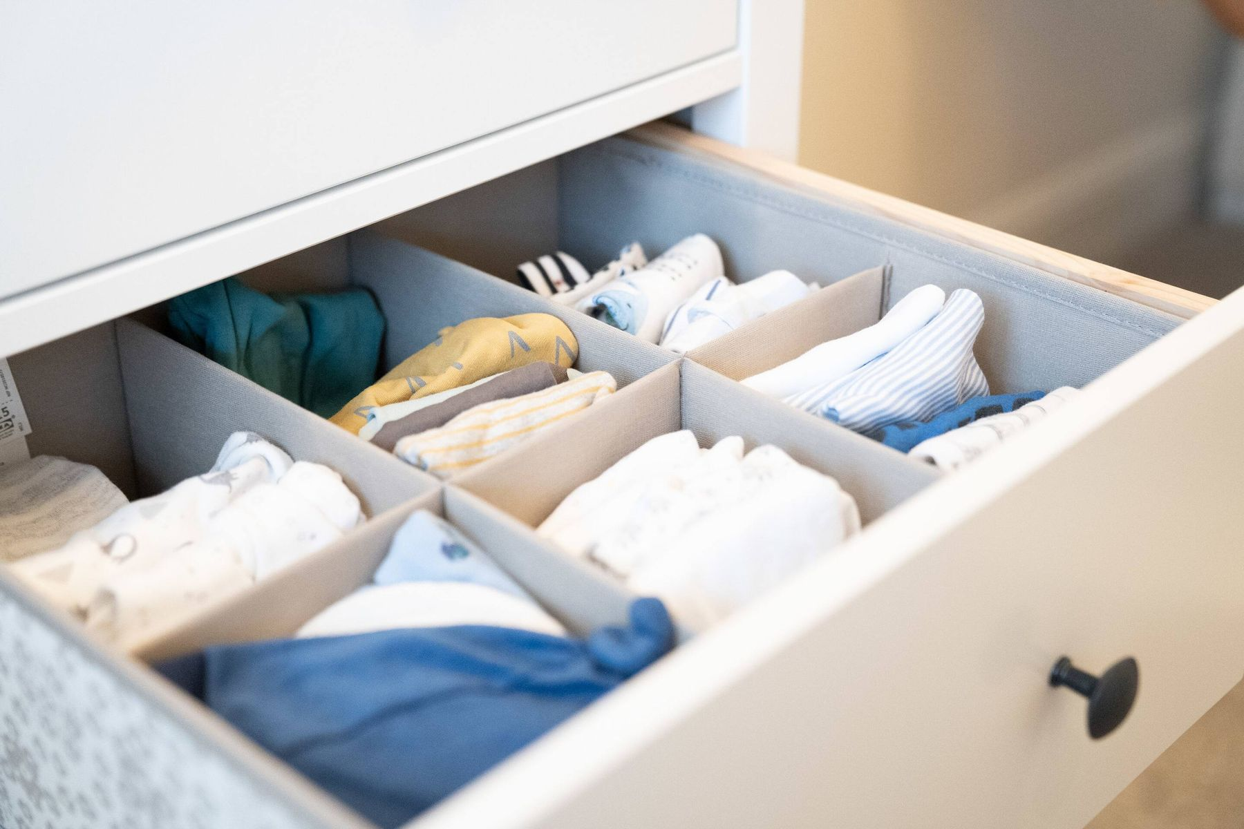 Baby clothes folded and organized in drawer