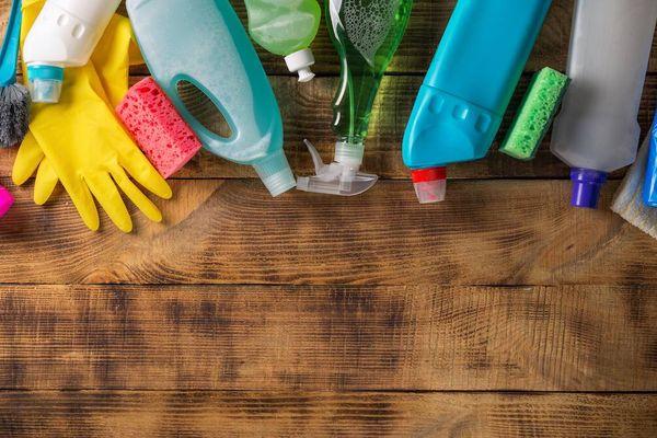 Frascos de produtos de limpeza e luvas de proteção sobre mesa de madeira