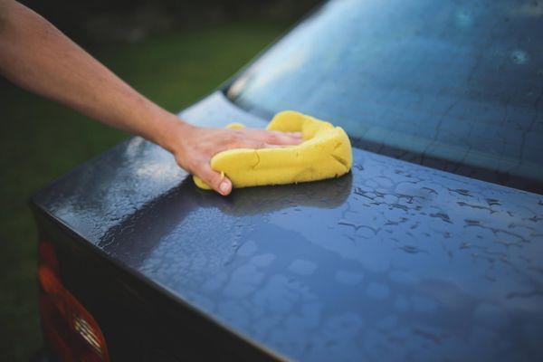 Händewaschen eines Autos mit einem gelben Lappen