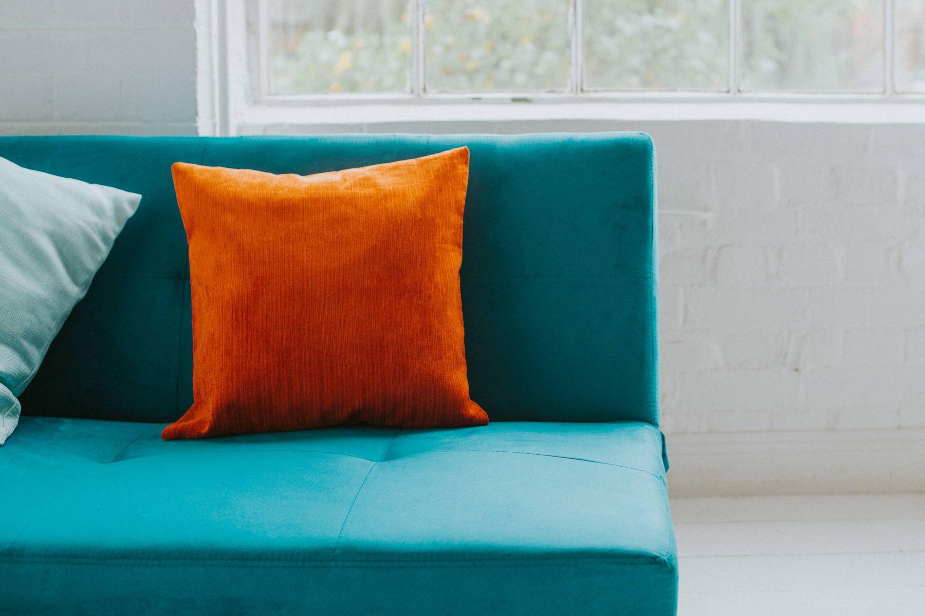 niebieska sofa z pomarańczową i zieloną poduszką