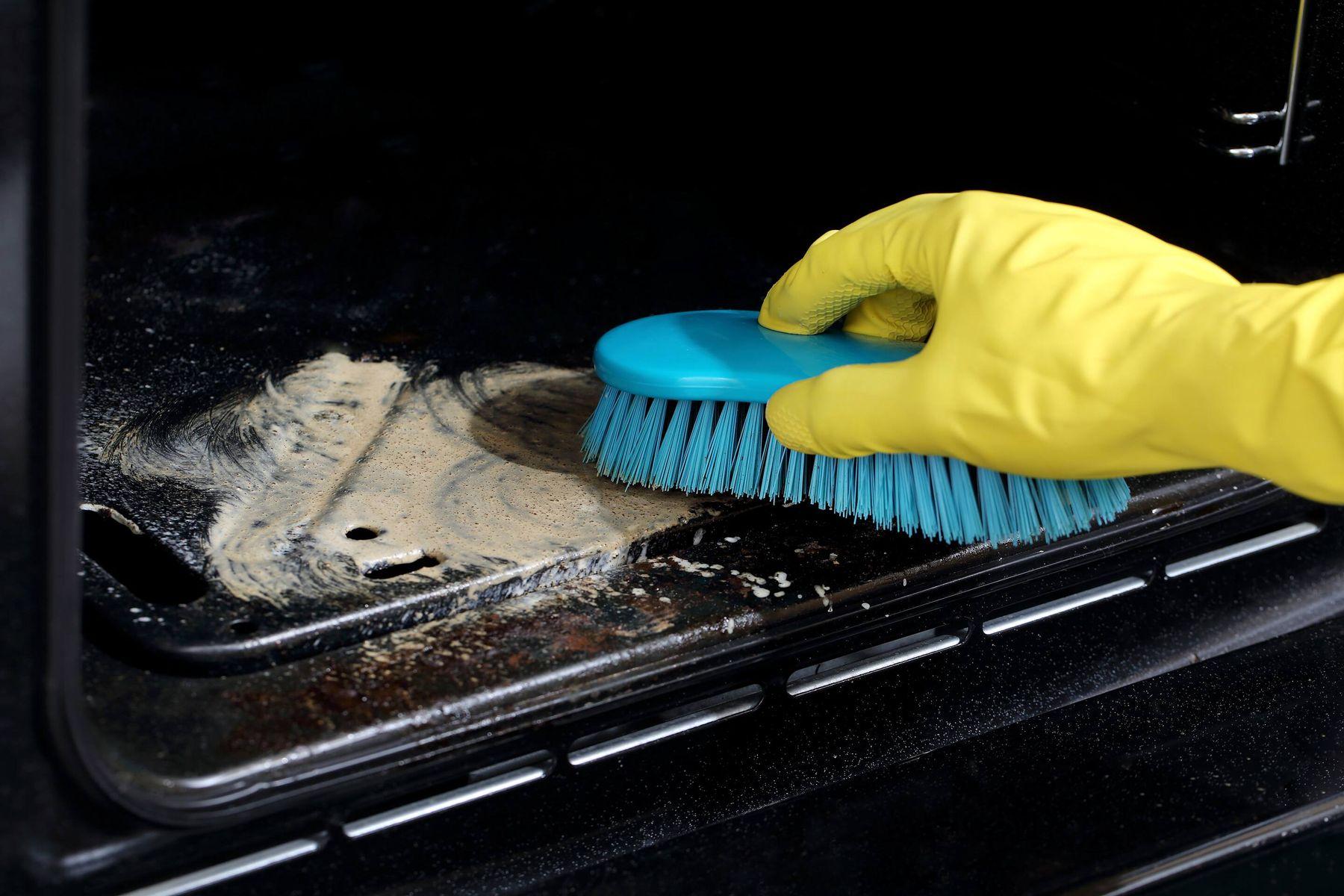 hand scrubbing interior of oven