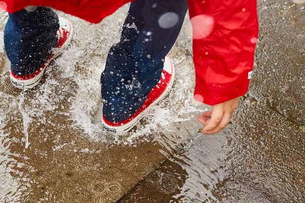 Jumping into a puddle with red canvas shoes