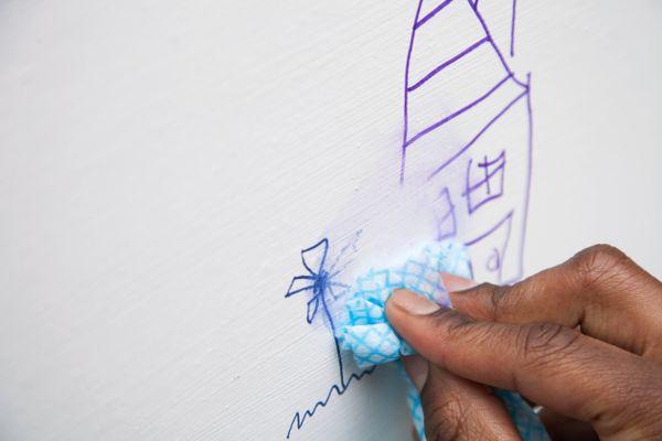 Parede com desenho de caneta sendo limpa com um pano