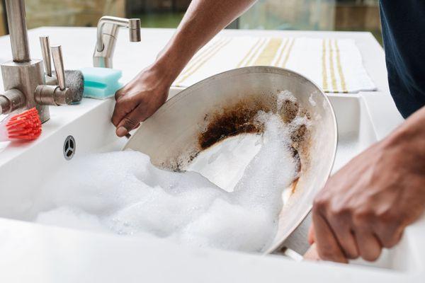 Pessoa lavando panela na pia da cozinha com detergente