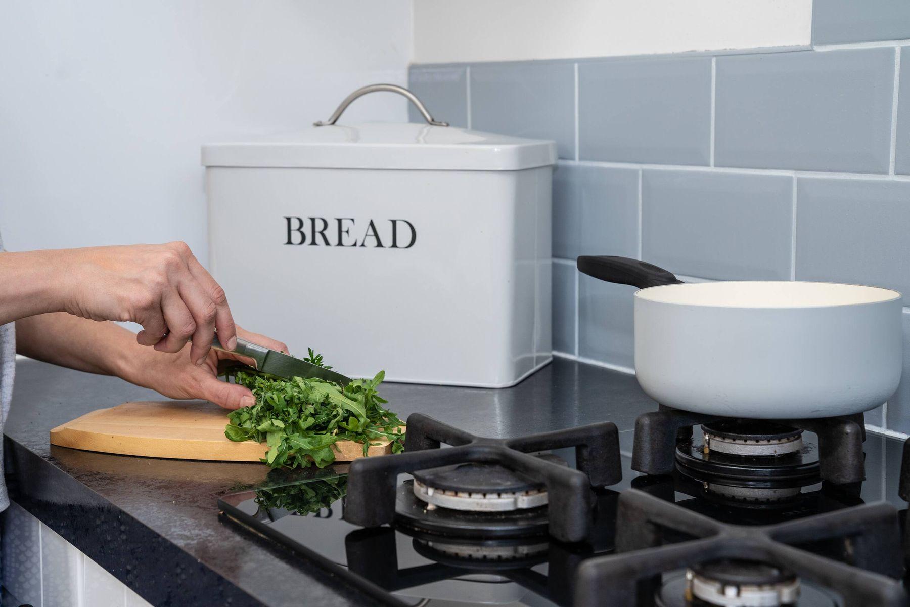 Kochen mit Brotbehälter, Frau, die Kräuter und einen Topf auf dem Ofen hackt