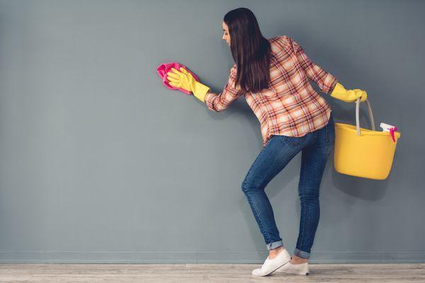 Mulher limpando a parede cinza com pano rosa