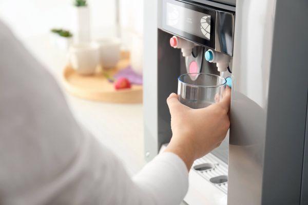 Manos de persona sirviéndose agua purificada de la heladera