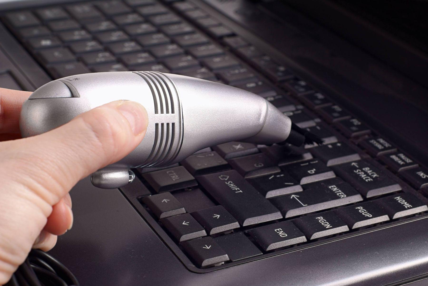 Dùng máy hút bụi để vệ sinh, hút bụi bẩn trong khe bàn phím laptop