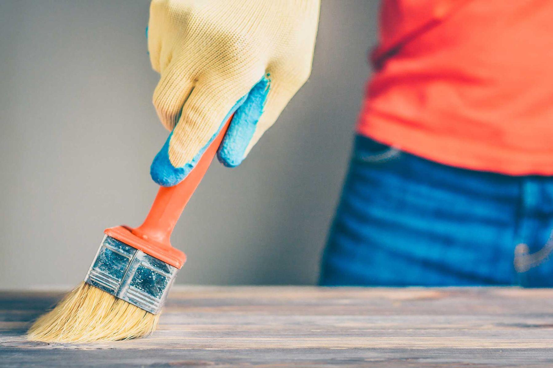 Persona pintando una mesa de madera