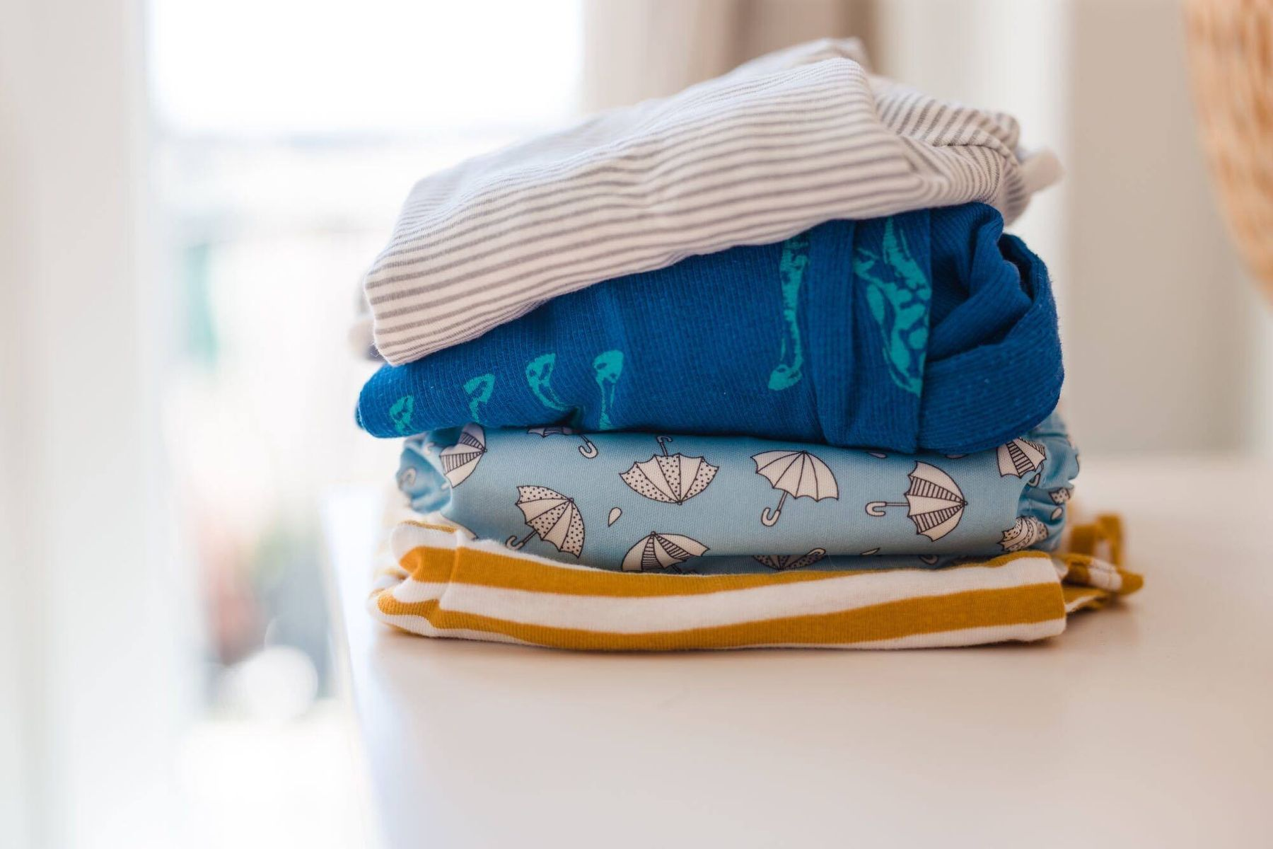 folded and stacked baby clothes