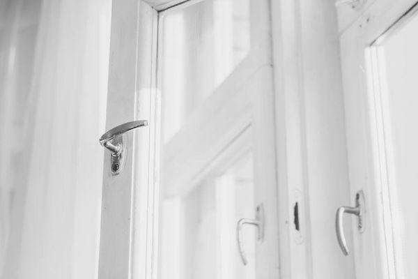 białe drzwi ze szkła i drewna z chromowaną klamką