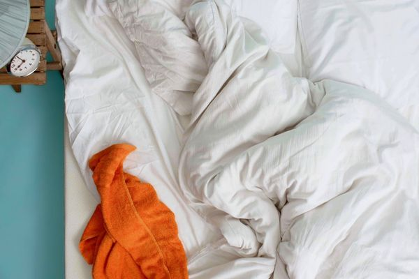 disorganized bed with white duvet and orange towel